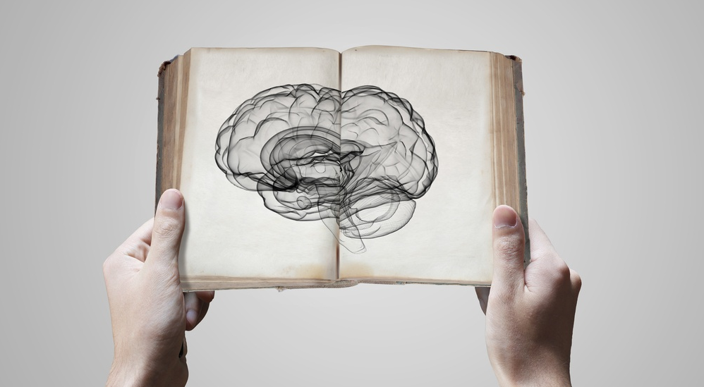 Close up of male hands holding opened book with brain picture-crop.png