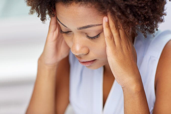 young woman holding head with headache